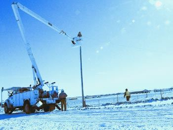 Electrical workers working on electrical pole in snow